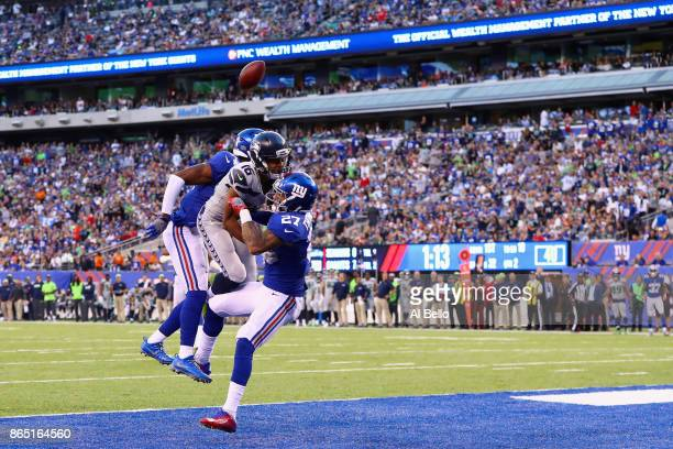 Tyler Lockett of the Seattle Seahawks is hurt on a pass breakup by Darian Thompson and Eli Apple of the New York Giants during the second quarter of...