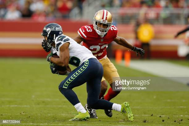 Tyler Lockett of the Seattle Seahawks is tackled by by Ahkello Witherspoon of the San Francisco 49ers at Levi's Stadium on November 26 2017 in Santa...
