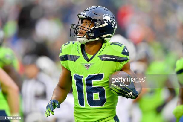 Tyler Lockett of the Seattle Seahawks looks at his first quarter touchdown catch on the scoreboard during the game against the Los Angeles Rams at...