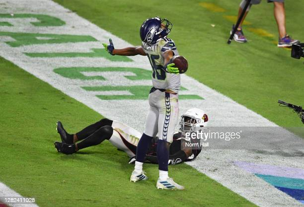 Tyler Lockett of the Seattle Seahawks reacts after catching a touchdown while being defended by Patrick Peterson of the Arizona Cardinals during the...