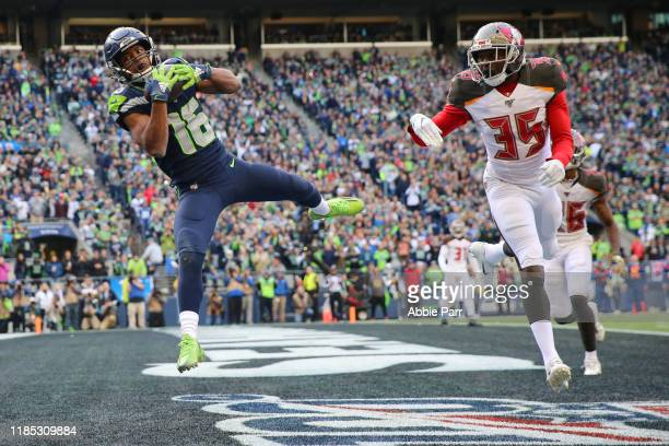 Tyler Lockett of the Seattle Seahawks scores a twoyard touchdown against Jamel Dean of the Tampa Bay Buccaneers in the third quarter during their...