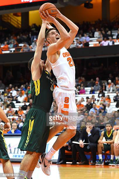 Tyler Lydon of the Syracuse Orange drives to the basket against the defense of Connor Mahoney of Le Moyne Dolphins during the first half at the...