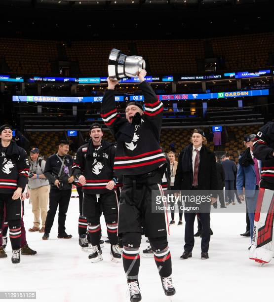 Tyler Madden of the Northeastern Huskies celebrates with the Beanpot trophy after a victory against the Boston College Eagles during NCAA hockey in...
