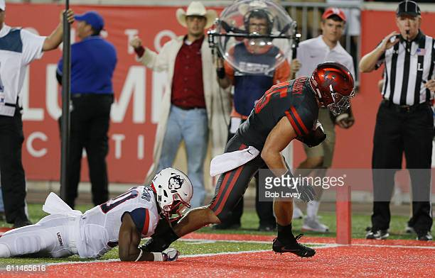 Tyler McCloskey of the Houston Cougars scores on a three yard pass as he drags Obi Melifonwu of the Connecticut Huskies into the endzone on September...