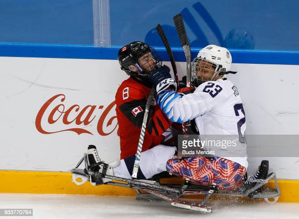 Tyler McGregor of Canada battles for the puck with Rico Roman of the United States in the Ice Hockey gold medal game between United States and Canada...