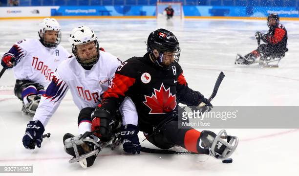 Tyler McGregor of Canada battles for the puck with Rolf Einar Pedersen of Norway in the Ice Hockey Preliminary Round Group A game between Canada and...