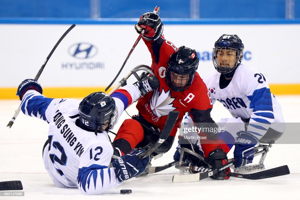 Tyler McGregor #8 of Canada battles for the puck with Sung Young Kim #12 of Korea in the Ice Hockey semi final game between Canada and Korea during day six of the PyeongChang 2018 Paralympic Games on March 15, 2018 in Gangneung, South Korea.