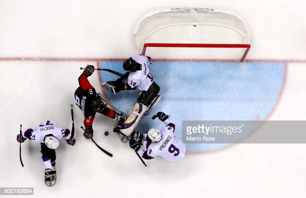 Tyler McGregor of Canada fails to score a goal over Kjell Hamar goaltender of Norway in the Ice Hockey Preliminary Round Group A game between Canada...