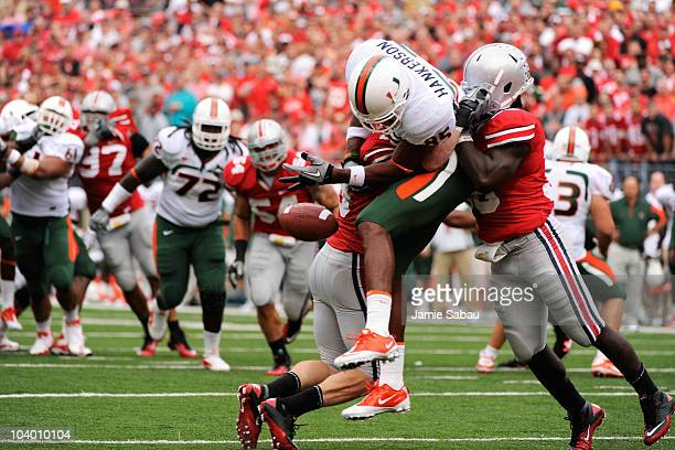 Tyler Moeller of the Ohio State Buckeyes and Brian Rolle of the Ohio State Buckeyes sandwich Leonard Hankerson of the Miami Hurricanes causing him to...