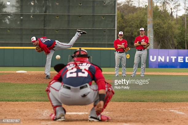 Tyler Moore and Mike Fontenot of the Washington Nationals look on as Jerry Blevins throws a warmup pitch to Jhonatan Solano during the spring...
