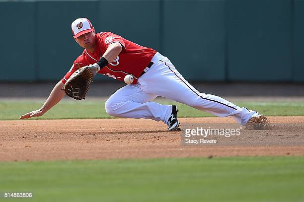 Tyler Moore of the Washington Nationals dives for a ground ball during the second inning of a spring training game against the New York Mets at Space...
