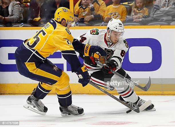 Tyler Motte of the Chicago Blackhawks battles against Matt Carle of the Nashville Predators during an NHL game at Bridgestone Arena on October 14...