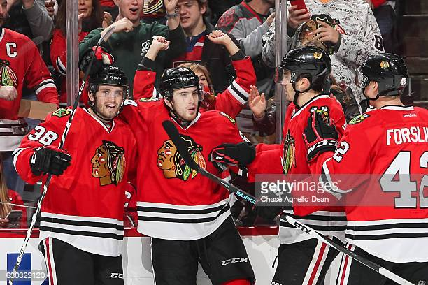 Tyler Motte of the Chicago Blackhawks celebrates with teammates including Ryan Hartman after scoring against the Ottawa Senators in the second period...