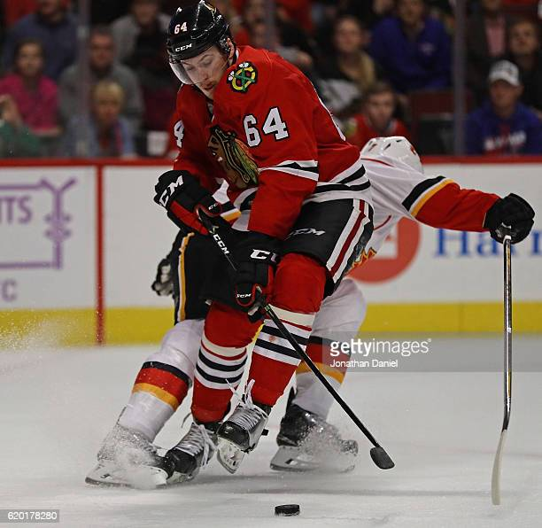 Tyler Motte of the Chicago Blackhawks gets tangled up with TJ Brodie of the Calgary Flames as he moves to score a third period goal at the United...