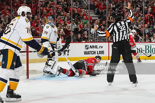 Tyler Motte of the Chicago Blackhawks lays in front of goalie Marek Mazanec of the Nashville Predators after taking a hit in the second period at the...