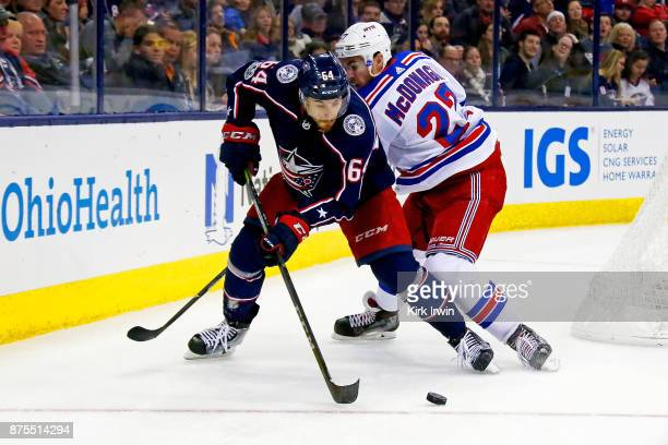 Tyler Motte of the Columbus Blue Jackets and Ryan McDonagh of the New York Rangers battle for control of the puck during the second period on...