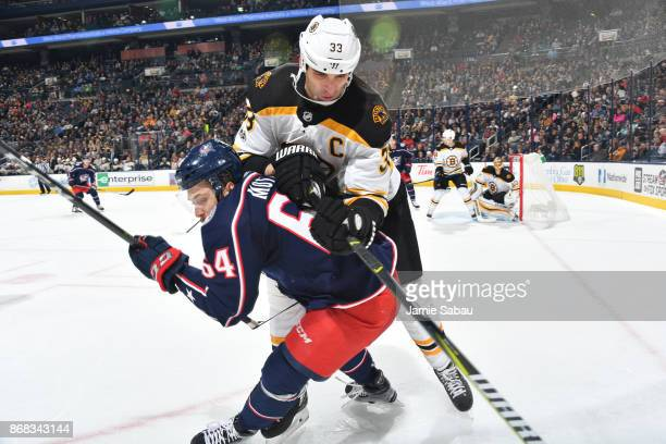 Tyler Motte of the Columbus Blue Jackets and Zdeno Chara of the Boston Bruins battle for a loose puck during the first period of a game on October 30...