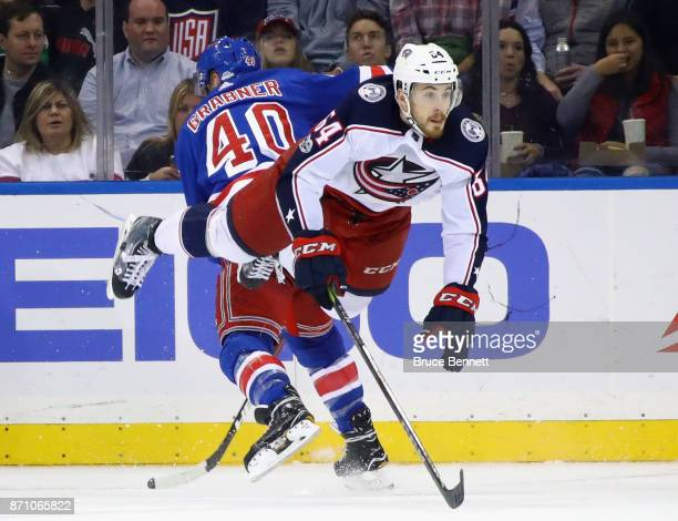 Tyler Motte of the Columbus Blue Jackets is tripped up by Michael Grabner of the New York Rangers during the third period at Madison Square Garden on...