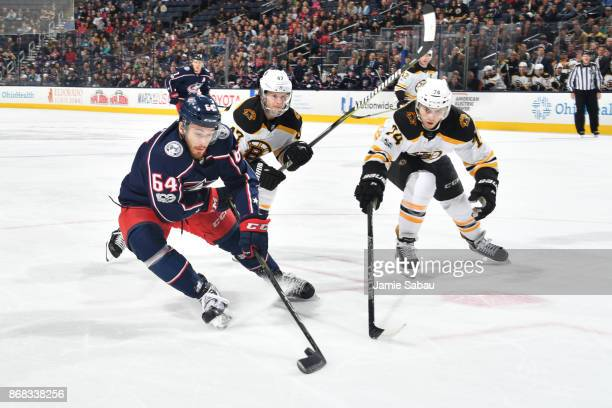 Tyler Motte of the Columbus Blue Jackets turns the puck away from Torey Krug and Jake DeBrusk of the Boston Bruins during the first period of a game...