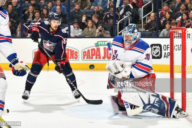 Tyler Motte of the Columbus Blue Jackets watches the puck as it bounces off goaltender Henrik Lundqvist of the New York Rangers during the first...