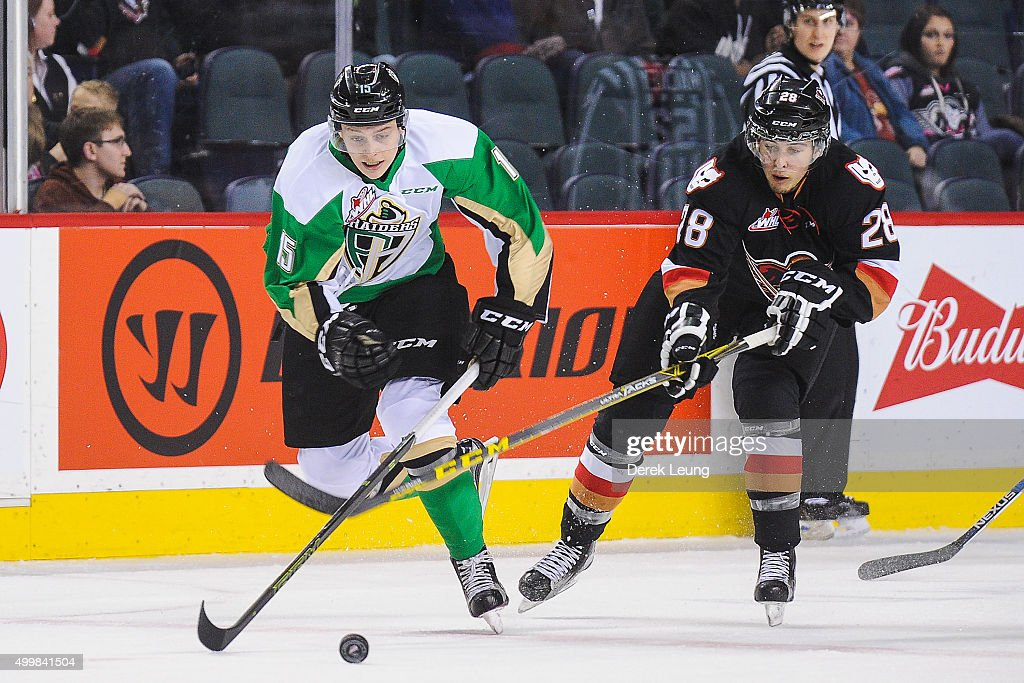 Tyler Mrkonjic #28 of the Calgary Hitmen checks Austin Glover #15 of the Prince Albert Raiders during a WHL game at Scotiabank Saddledome on December 3, 2015 in Calgary, Alberta, Canada.
