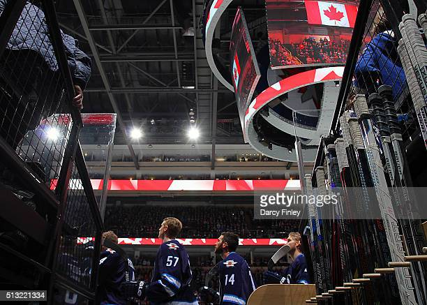 Tyler Myers and Anthony Peluso of the Winnipeg Jets stand on the bench during the singing of the National anthems prior to puck drop against the...