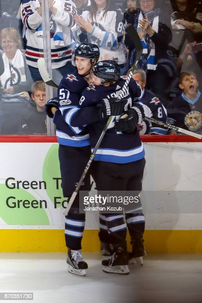 Tyler Myers and Brendan Lemieux of the Winnipeg Jets celebrate a third period goal against the Pittsburgh Penguins at the Bell MTS Place on October...