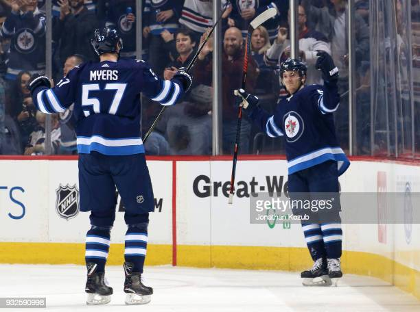 Tyler Myers and Jack Roslovic of the Winnipeg Jets celebrate after a first period goal against the Chicago Blackhawks at the Bell MTS Place on March...