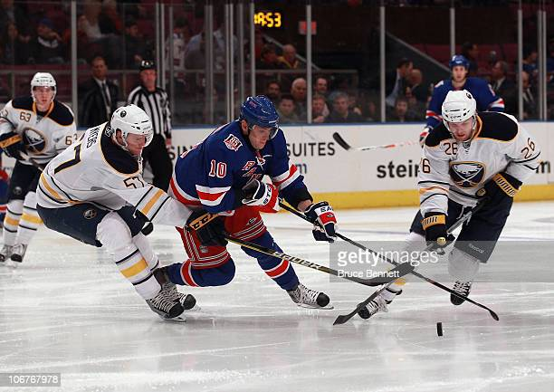 Tyler Myers and Thomas Vanek of the Buffalo Sabres trip up Marian Gaborik of the New York Rangers at Madison Square Garden on November 11, 2010 in...