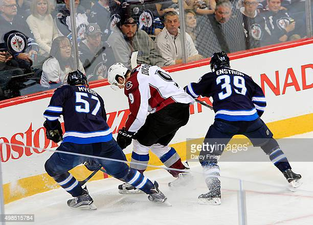 Tyler Myers and Toby Enstrom of the Winnipeg Jets battles for the puck against Matt Duchene of the Colorado Avalanche during second period action at...