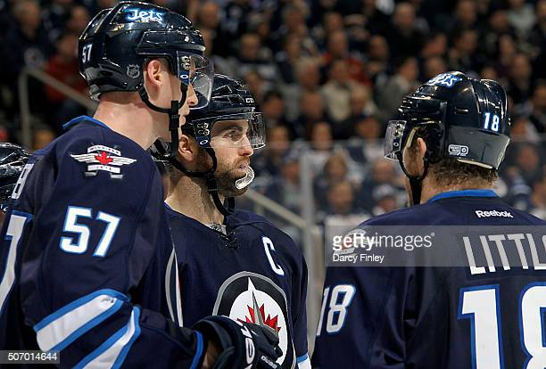 Tyler Myers Andrew Ladd and Bryan Little of the Winnipeg Jets discuss strategy during a third period stoppage in play against the Arizona Coyotes at...
