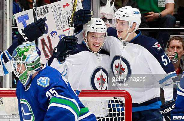 Tyler Myers congratulates Marko Dano of the Winnipeg Jets who scored on Jacob Markstrom of the Canucks during their NHL game at Rogers Arena March 14...