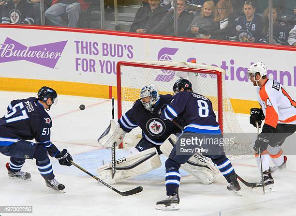 Tyler Myers goaltender Ondrej Pavelec and Jacob Trouba of the Winnipeg Jets and Sean Couturier of the Philadelphia Flyers keep an eye on the flying...