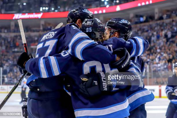 Tyler Myers Mathieu Perreault and Nikolaj Ehlers of the Winnipeg Jets celebrate a first period goal against the Tampa Bay Lightning at the Bell MTS...