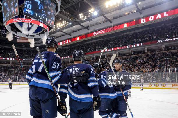 Tyler Myers Nikolaj Ehlers Mathieu Perreault and Bryan Little of the Winnipeg Jets celebrate a first period goal against the Edmonton Oilers at the...