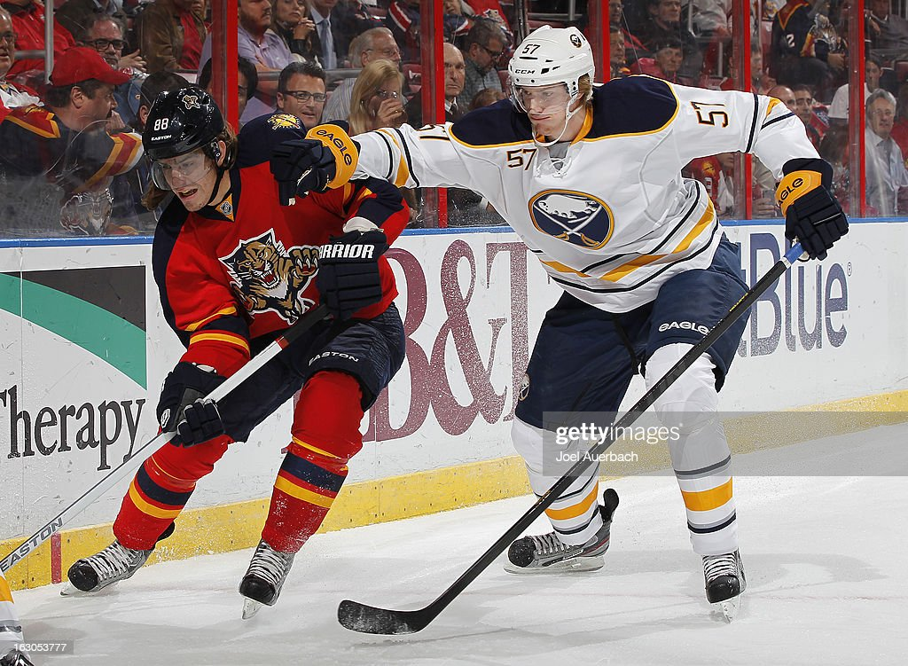 Tyler Myers #57 of the Buffalo Sabres and Peter Mueller #88 of the Florida Panthers battle along the boards at the BB&T Center on February 28, 2013 in Sunrise, Florida. The sabers defeated the Panthers 4-3 in a shootout.