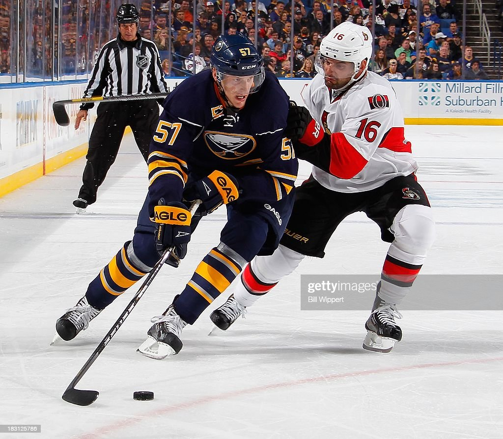 Tyler Myers #57 of the Buffalo Sabres controls the puck against Clarke MacArthur #16 of the Ottawa Senators on October 4, 2013 at the First Niagara Center in Buffalo, New York.