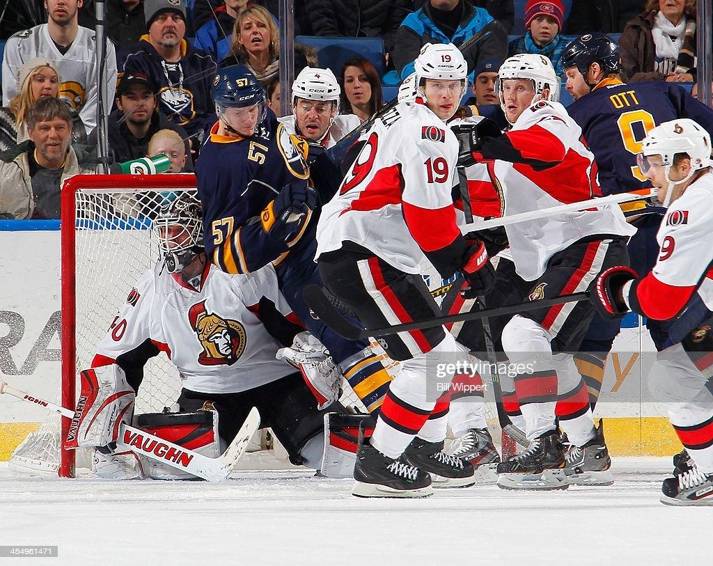 Tyler Myers #57 of the Buffalo Sabres crashes between goaltender Robin Lehner #40, Chris Phillips #4 and Jason Spezza #19 of the Ottawa Senators on December 10, 2013 at the First Niagara Center in Buffalo, New York.