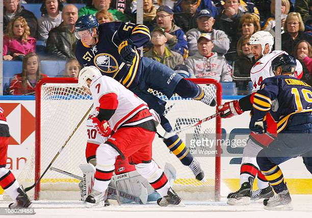 Tyler Myers of the Buffalo Sabres flips over goaltender Cam Ward of the Carolina Hurricanes behind Ian White at HSBC Arena on January 1 2011 in...