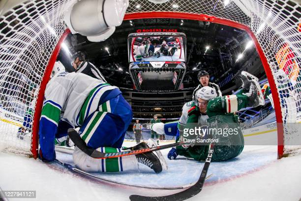 Tyler Myers of the Vancouver Canucks battles against Luke Kunin of the Minnesota Wild as Oscar Fantenberg falls during the second period in Game...