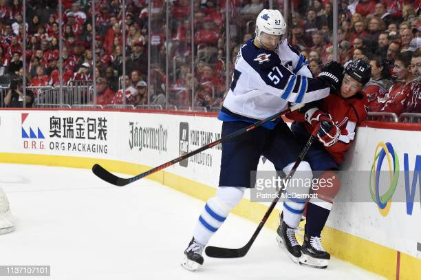 Tyler Myers of the Winnipeg Jets and Jakub Vrana of the Washington Capitals collide in the third period at Capital One Arena on March 10 2019 in...
