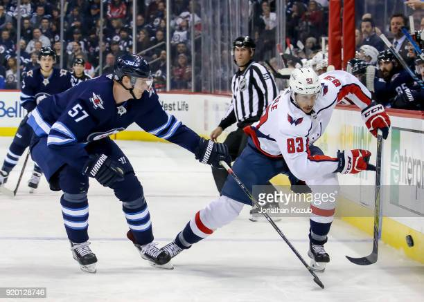 Tyler Myers of the Winnipeg Jets and Jay Beagle of the Washington Capitals follow the loose puck down the ice during first period action at the Bell...