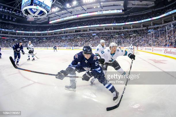 Tyler Myers of the Winnipeg Jets and Justin Braun of the San Jose Sharks battle for the puck during first period action at the Bell MTS Place on...