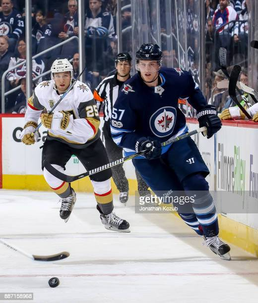 Tyler Myers of the Winnipeg Jets and Stefan Matteau of the Vegas Golden Knights chase the puck down the ice during first period action at the Bell...