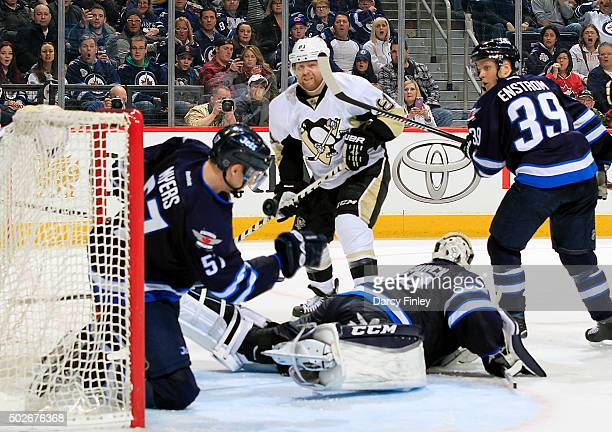 Tyler Myers of the Winnipeg Jets backs up goaltender Connor Hellebuyck and makes a save on the goalline on a shot by Nick Bonino of the Pittsburgh...