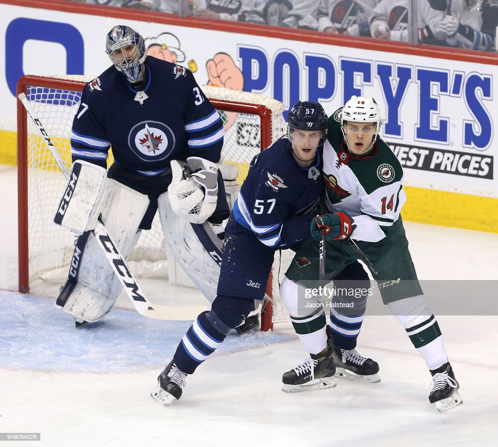 Tyler Myers #57 of the Winnipeg Jets battles Joel Eriksson Ek #14 in Game Five of the Western Conference First Round during the 2018 NHL Stanley Cup Playoffs against the Minnesota Wild on April 20, 2018 at Bell MTS Place in Winnipeg, Manitoba, Canada.