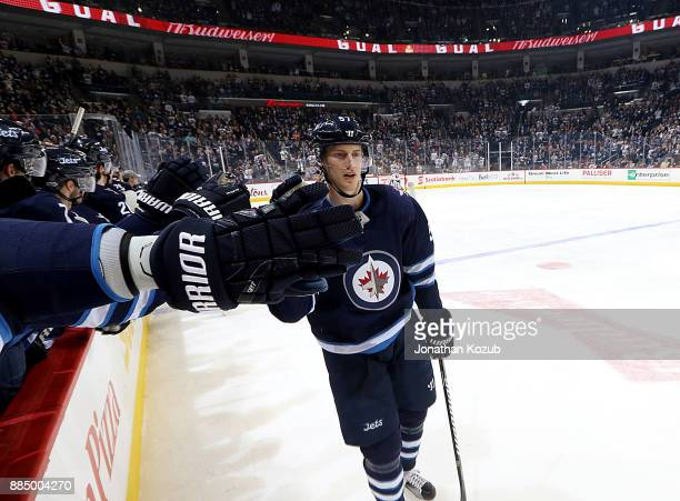 Tyler Myers of the Winnipeg Jets celebrates his second period goal against the Ottawa Senators with teammates at the bench at the Bell MTS Place on...