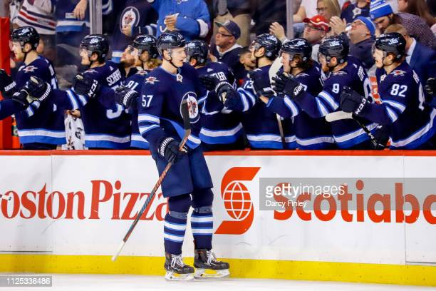 Tyler Myers of the Winnipeg Jets celebrates his third period goal against the Ottawa Senators with teammates at the bench at the Bell MTS Place on...
