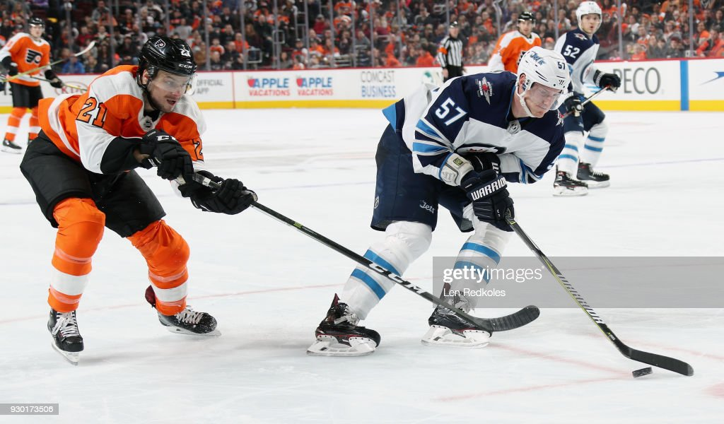 Tyler Myers #57 of the Winnipeg Jets controls the puck in the corner while being pursued by Scott Laughton #21 of the Philadelphia Flyers on March 10, 2018 at the Wells Fargo Center in Philadelphia, Pennsylvania. The Flyers went on to defeat the Jets 2-1.