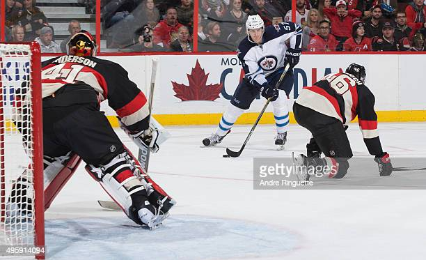 Tyler Myers of the Winnipeg Jets drives to the net with the puck on a scoring chance against Craig Anderson and Patrick Wiercioch of the Ottawa...